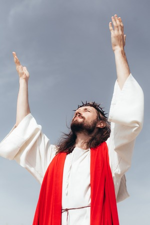 low angle view of Jesus in robe, red sash and crown of thorns standing with raised hands against grey sky Stock Photo
