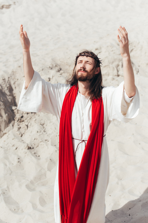 Jesus in robe, red sash and crown of thorns standing with raised hands and praying in desert