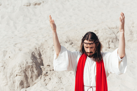 Jesus standing with raised hands and praying in desert