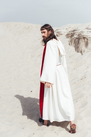 back view of Jesus in robe, red sash and crown of thorns walking in desert