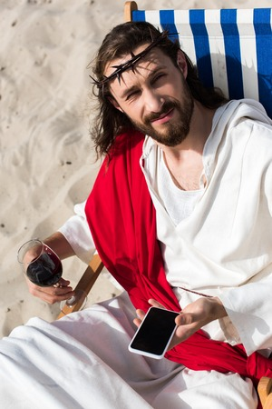 Jesus resting on sun lounger with glass of wine and holding smartphone with blank screen in desert Stock Photo