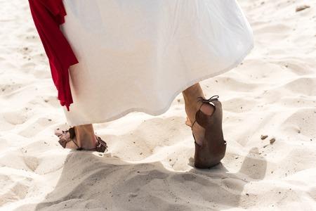 Imagen recortada de Jesús en túnica, sandalias y fajín rojo caminando sobre la arena en el desierto