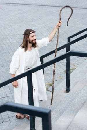 high angle view of cheerful Jesus in robe and crown of thorns walking on stairs with staff Stock Photo