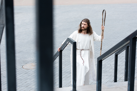 high angle view of Jesus in robe and crown of thorns walking on stairs with staff Stock Photo