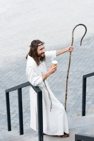 high angle view of Jesus in robe and crown of thorns holding disposable coffee cup and staff on street
