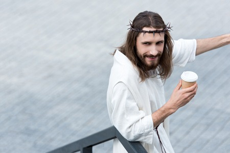 cheerful Jesus in robe and crown of thorns holding disposable coffee cup on street