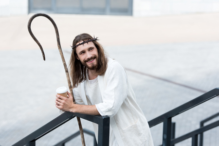 smiling Jesus in robe and crown of thorns holding disposable coffee cup and leaning on railing on street Stock Photo