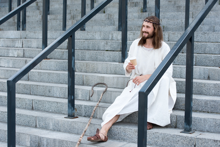 cheerful Jesus in robe and crown of thorns sitting on stairs and holding disposable coffee cup on street