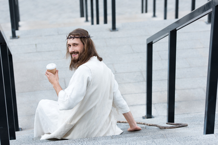 back view of smiling Jesus in robe and crown of thorns sitting on stairs and holding disposable coffee cup on street