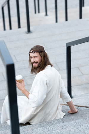 rear view of smiling Jesus in robe and crown of thorns sitting on stairs and holding disposable coffee cup on street