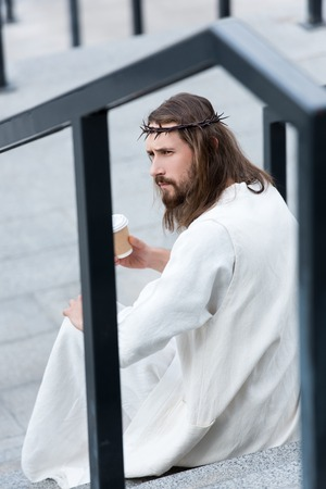 side view of serious Jesus in robe and crown of thorns sitting on stairs and holding disposable coffee cup on street