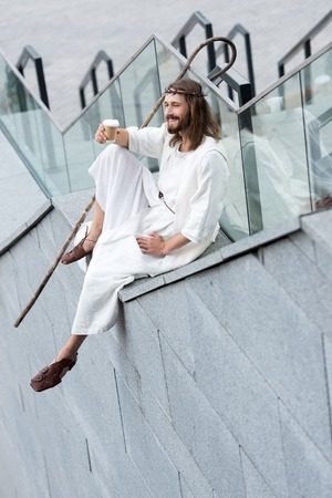 smiling Jesus in robe and crown of thorns sitting on staircase side and holding disposable coffee cup