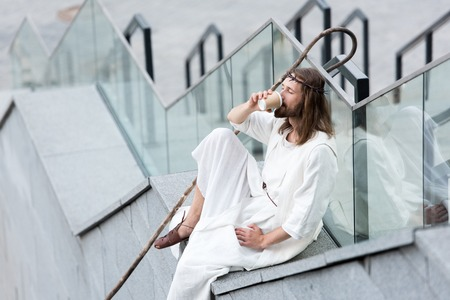 Jesus in robe and crown of thorns sitting on staircase side and drinking coffee from disposable coffee cup