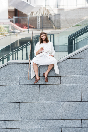 cheerful Jesus in robe and crown of thorns sitting on staircase side and holding coffee to go Stock Photo
