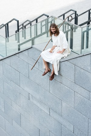 smiling Jesus in robe and crown of thorns sitting on staircase side, holding disposable coffee cup and looking down
