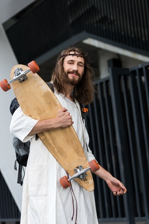 low angle view of cheerful Jesus in robe and crown of thorns holding skateboard Stock Photo - 110165342