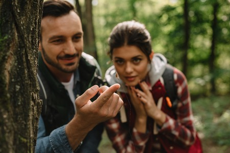 selective focus of couple of travelers looking at spider on net in forest