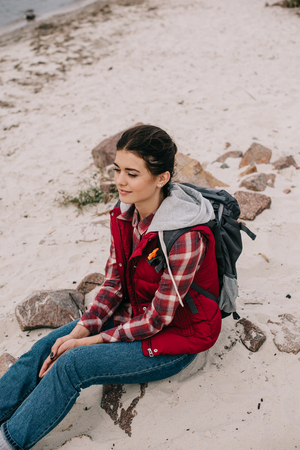 pensive woman with backpack resting on rocks on sandy beach