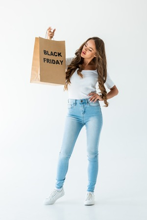 young woman holding shopping bag with black friday sign, isolated on white