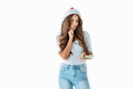attractive sly girl in santa hat holding dollar banknotes, isolated on white