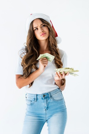 thoughtful girl in santa hat holding dollar banknotes, isolated on white Stock Photo