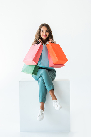 smiling shopaholic sitting on white cube with shopping bags, isolated on white Stockfoto