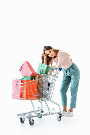 beautiful tired girl with shopping cart and bags, isolated on white