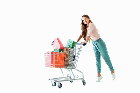 beautiful cheerful girl with shopping cart and bags, isolated on white
