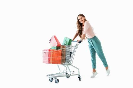 schönes fröhliches Mädchen mit Einkaufswagen und Taschen, lokalisiert auf Weiß Standard-Bild