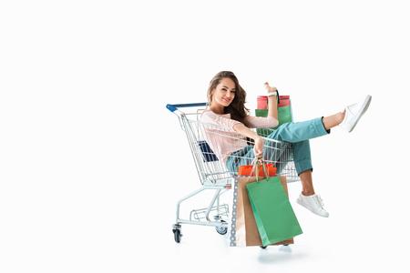 gelukkig mooi meisje zit in winkelwagen met zakken, geïsoleerd op wit Stockfoto