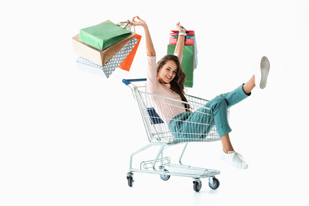 excited girl with shopping bags sitting in shopping cart, isolated on white
