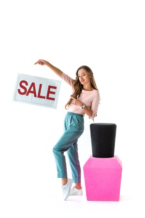 attractive young woman pointing at sale symbol near big nail polish, manicure concept, isolated on white Banque d'images - 109810684