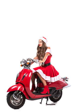attractive brunette girl in santa costume driving red scooter, isolated on white