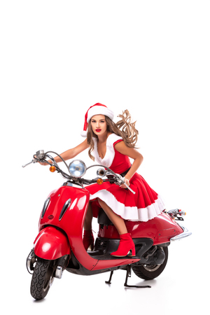 beautiful young woman in santa costume driving red scooter, isolated on white Stock Photo