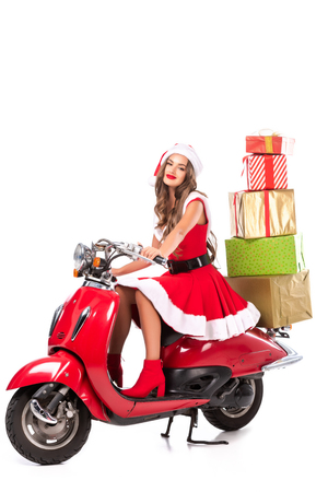 happy brunette girl in santa costume driving red scooter with presents, isolated on white