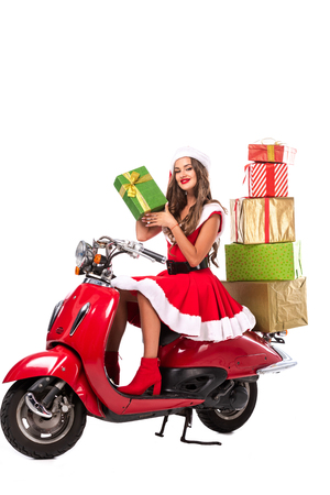 attractive girl in santa costume driving red scooter with gift boxes, isolated on white