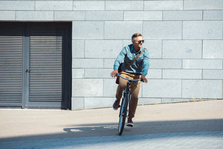 stylish middle aged man in sunglasses riding bicycle and looking away on street