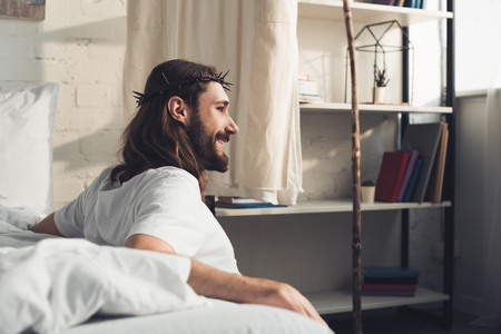 side view of smiling Jesus sitting on floor near bed during morning time in bedroom at home Stock Photo