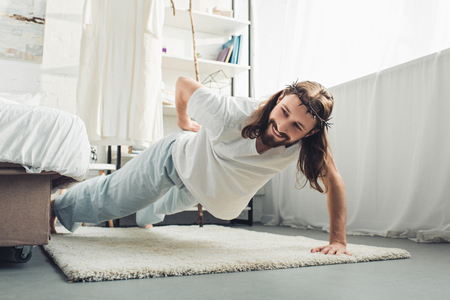 smiling Jesus in crown of thorns doing push ups on one hand during morning time in bedroom at home