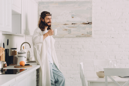 cheerful Jesus in crown of thorns standing with cup of coffee in kitchen at home