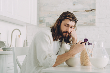 tired Jesus eating corn flakes on breakfast in kitchen at home Archivio Fotografico