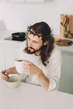 high angle view of Jesus eating corn flakes and drinking coffee on breakfast in kitchen at home Imagens