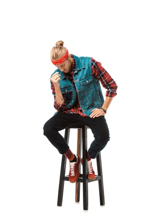 hipster man in denim vest and red checkered shirt sitting on chair isolated on white
