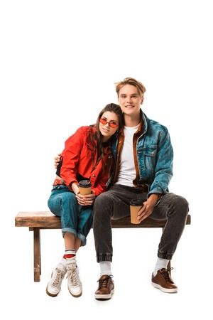young hipster couple with disposable cups of coffee sitting on bench isolated on white