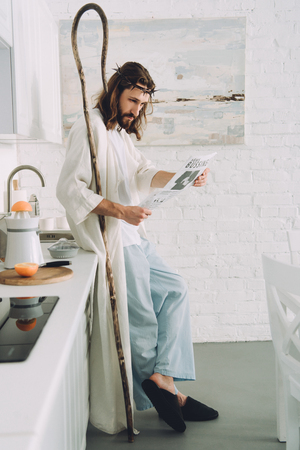 focused Jesus with wooden staff reading business newspaper in kitchen at home Stockfoto