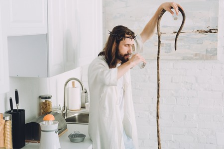 tired Jesus in crown of thorns drinking water and standing with wooden staff in kitchen at home Stockfoto