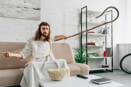 serious Jesus sitting on sofa with wooden staff and watching tv at home