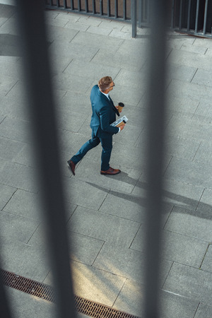selective focus of businessman with coffee to go and newspaper walking on street Imagens