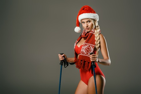 beautiful woman in red swimming suit and santa claus hat with skiing equipment posing on grey backdrop