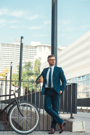handsome businessman holding coffee to go and looking away while standing near bicycle on street